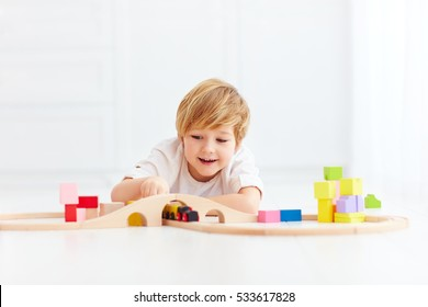 cute kid playing with toy railway at home