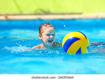 cute kid playing water sport games in pool
