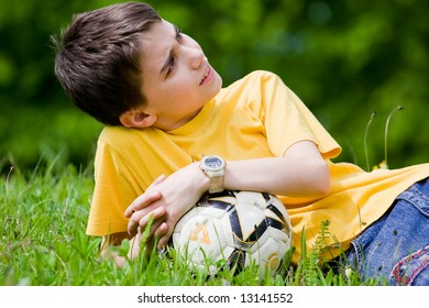 Cute kid resting in meadow after soccer game