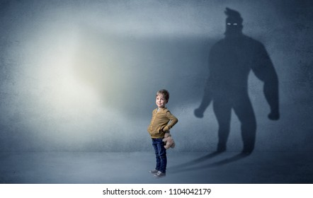 Cute kid in a room with plush on his hand and hero shadow on his background