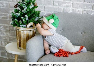 Cute kid as Santa helper for Christmas wearing elf hat playing with Christmas tree. Holiday season at home