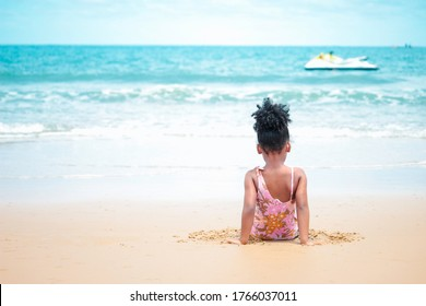 Cute kid setting and having fun on sandy summer beach with blue sea, happy little girl playing on tropical beach