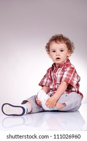 Cute kid sitting and holding his right leg while looking at the camera, on gray background