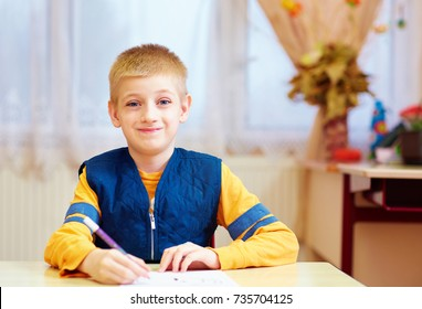 cute kid with special need sitting at the desk in classroom