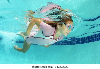 cute kid swimming underwater in pool