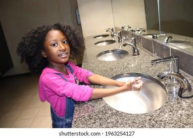 Cute Kid washing hands in public bathroom sink