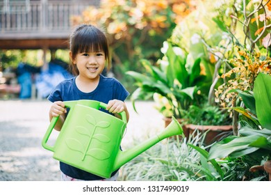 Cute kid watering a tree for help to prevent global warming or climate change and save the earth. Gardening activity concept of Mother Earth Day to encourage people about the environmental protection.