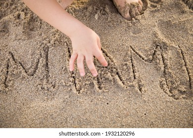 Cute kid wrote the word Miami in the sand. Vacation concept. Selective focus
