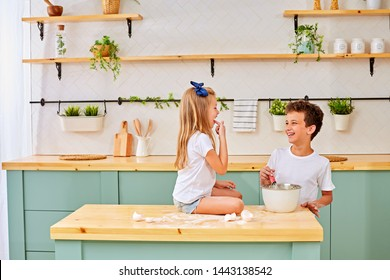 Cute kids, adorable little girl and boy making dough for a cake. Children mix flour, eggs and milk baking apple pie in sunny white kitchen with modern appliances