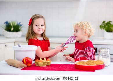 Cute kids, adorable little girl and blond curly boy making dough for a cake. Children mix flour, eggs and milk baking apple pie in sunny white kitchen with modern appliances. Family cooking at home.