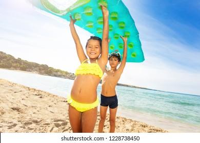 Cute kids with air mattress overhead on the beach