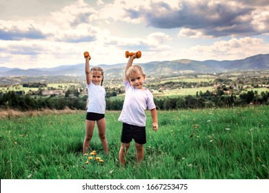 Cute kids, boy and girl, doing the morning exercises with dumbbells on the top of the mountains in summer nature, morning exercises, sport and healthy lifestyle, outside