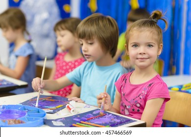 Cute kids doing their craft, painting at kindergarten
