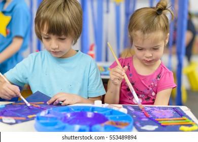 Cute kids doing their craft, painting at kindergarten