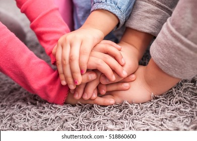 cute kids hands together on gray wool carpet, cheering pose