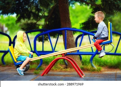 cute kids having fun on seesaw at playground