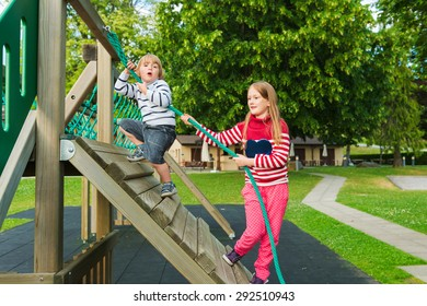 Cute kids having fun on playground, wearing warm pullovers