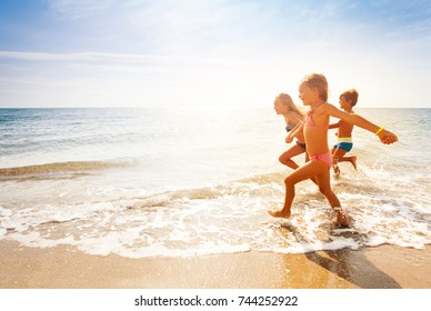 Cute kids having fun on sandy beach in summer