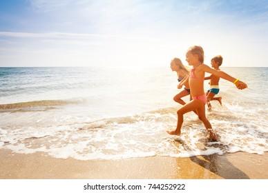 Cute-Kinder, die sich im Sommer am Sandstrand amüsieren