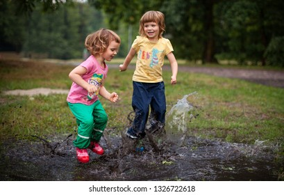 Cute Kids Jumping into Water Puddle