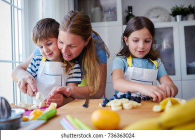 Cute kids with mother preparing a healthy fruit snack in kitchen