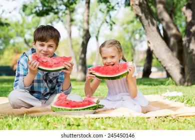 Cute kids in park eating juicy watermelon