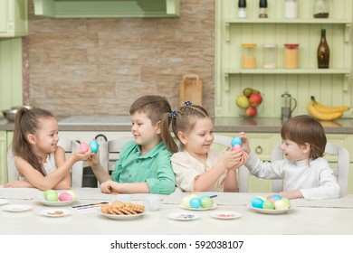 Cute kids playing Easter eggs at the table and laugh