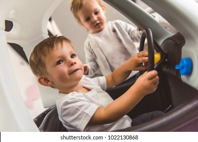 Cute kids are playing together. Boy is sitting in the toy car, girl is standing near