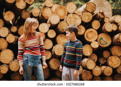 Cute kids playing together in a spring forest next to wooden logs