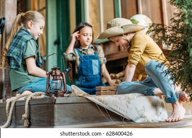 cute kids playing treasure hunt with map on porch