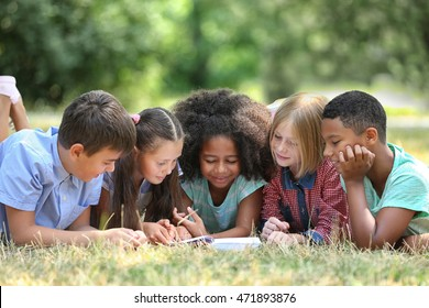 Cute kids reading book on green grass