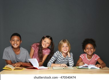 Cute kids reading books on grey background