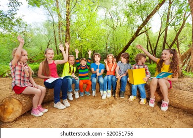 Cute kids reading books outdoor sitting on the log