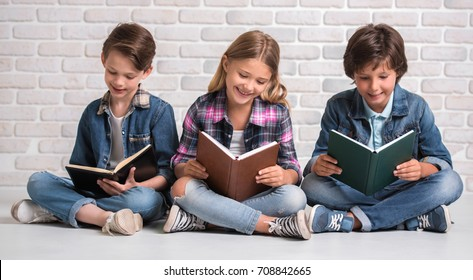 Cute kids are reading books and smiling while sitting on the floor