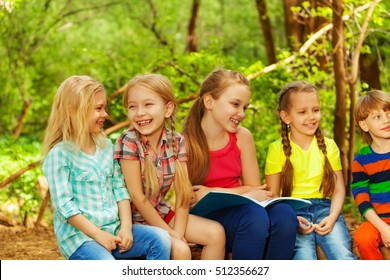 Cute kids reading fairy-tales sitting in the park