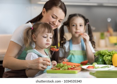 Cute kids sisters tasting vegetables as they prepare a meal with their mother in the kitchen