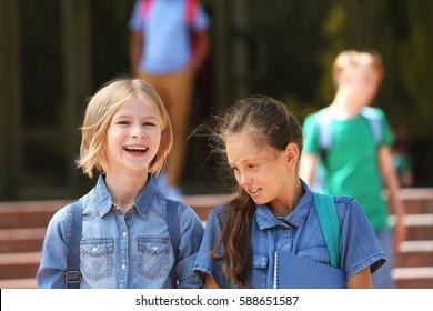 Cute kids standing near school