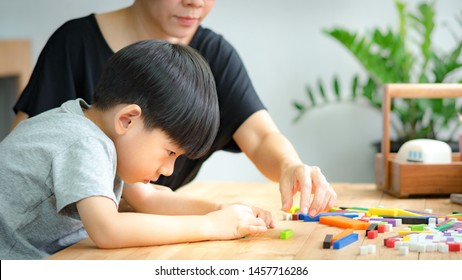 Cute kindergarten Asian boy learning with mother about numeracy, adding - subtracting and counting through colorful cuisenaire rods. Early math, Cognitive skills, Problem solving, Child development.