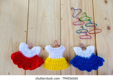 Cute knit colorful mini dresses hung on wooden background made of yarn. Idea concept with copy space.