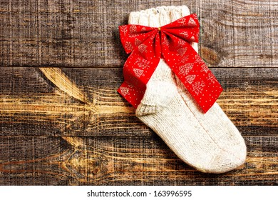 Cute knitted Christmas sock hanging on rustic  background