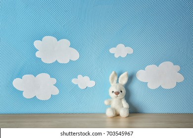 Cute knitted toy bunny on wooden table near blue wall with paper clouds