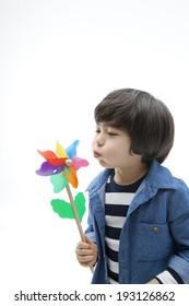Cute Korean kid playing with pinwheel