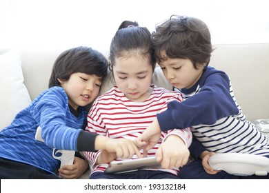 Cute Korean kids playing with gaming console