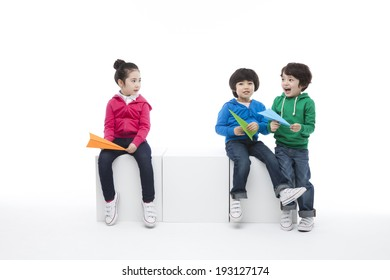 Cute Korean kids playing with paper airplanes