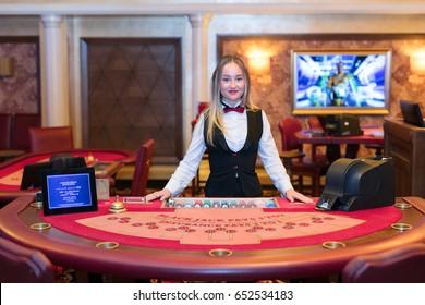 Cute lady casino dealer at Black Jack table.