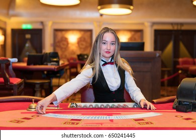 Cute lady casino dealer at poker table.