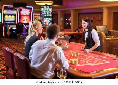 Cute lady casino dealer at Roulette table. Happy couple is playing Roulette.