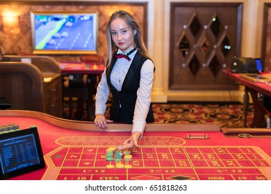 Cute lady casino dealer at Roulette table.