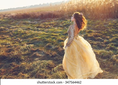 Cute lady walking through the field. Sunset background