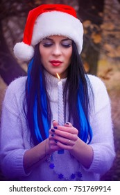 Cute lady in xmas hat with blue hair locks at magical winter atmosphere. Christmas fortune telling of young girls on a betrothed. The magic moments of the winter holidays
